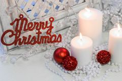 White burning candles, Merry Cristmas red inscription. White burning candles and Merry Cristmas red gleaming inscription on a white wooden background Royalty Free Stock Photos