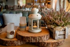 White burning lantern, heather in wooden box on a wooden table decorated in autumnal style, pine cornes, walnuts and stock photography
