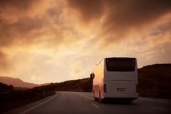 White bus driving on road towards the setting sun. White bus driving on road with sunset view Stock Photos