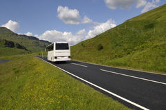 White bus on mountain road Stock Image