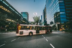 White Bus on Road Near in High Rise Building during Daytime Royalty Free Stock Photography