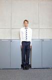 White business man standng straight between cabinets in office Royalty Free Stock Photos