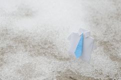 White business origami suit with blue tie on snow ground Stock Photography
