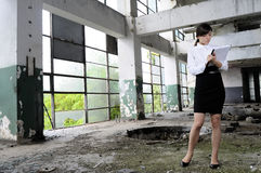 White business woman evaluating buildings. Successful young person writing report about demolished building for real estate industry Royalty Free Stock Images