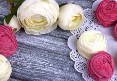 White buttercup flowers ranunculus white and pink zephyr marshmallows lacy paper napkin on gray wooden background. Copy space.  Stock Photography