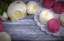 White buttercup flowers ranunculus white and pink zephyr marshmallows lacy paper napkin on gray wooden background. Copy space. White buttercup flowers Royalty Free Stock Images