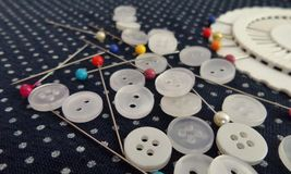 White buttons and colourful pin on polka dot cloth in dress maker shop Royalty Free Stock Photo