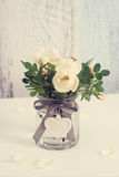 White buttons of hedge rose in glass can Stock Images