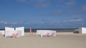 White cabanas at the seaside. With recliner chairs on a sandy tropical beach with a calm blue ocean in the background on a sunny summer day Stock Images