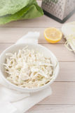 White cabbage cole slaw in white bowl. On light wooden background Royalty Free Stock Photography