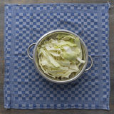 White cabbage fresh washed and cut in a metal colander on a blue Royalty Free Stock Images