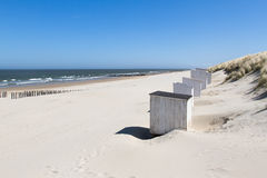 White cabins at a sunny beach. White cabins (or beach houses) standing against the grass covered dunes on a deserted beach at Domburg in Holland Royalty Free Stock Photos