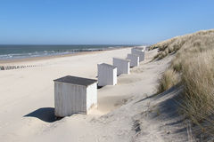 White cabins at a sunny beach. White cabins (or beach houses) standing against the grass covered dunes on a deserted beach at Domburg in Holland Stock Image
