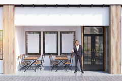 White cafe exterior, posters, man Royalty Free Stock Image