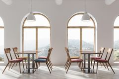 White cafe interior. Modern white cafe interior with a wooden floor and square tables with blue and red chairs near them. Large windows. 3d rendering Royalty Free Stock Photos