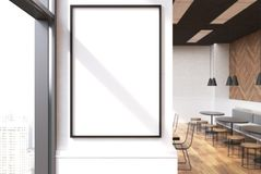 White cafe interior, poster close up. Close up of a vertical framed poster on a cafe wall. Large windows, white and wooden walls and round tables with sofas and Stock Images