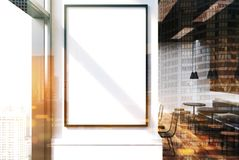 White cafe interior, poster close up toned. Close up of a vertical framed poster on a cafe wall. Large windows, white and wooden walls and round tables with Royalty Free Stock Image