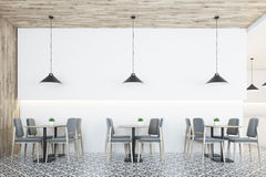 White cafe, wooden ceiling. White cafe interior with a wooden wall and a ceiling, a geometric floor pattern, square tables and gray chairs near them. Low Royalty Free Stock Image