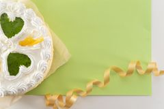 White cake on a colored background with ribbons shot from above stock photo