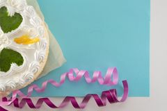 White cake on a colored background with ribbons shot from above stock image