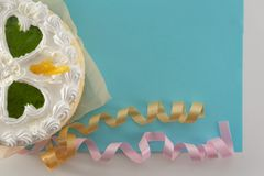 White cake on a colored background with ribbons shot from above royalty free stock photography