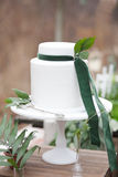 White cake. Decorated with green velvet ribbons and leaves with silver cake shovel on white stand and geen and beige background Stock Images