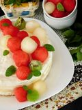White cake decorated with watermelon, melon and kiwi ball-shaped pieces royalty free stock image