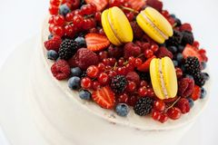 White cake with fruits and makarons Stock Photos