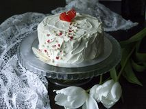 White cake with red chocolate heart on a glass stand on a dark background with lace fabric and white tulips. Valentine`s Day Cake. Copy space, Selective focus royalty free stock photos
