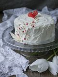 White cake with red chocolate heart on a glass stand on a dark background with lace fabric and white tulips. Valentine`s Day Cake. Copy space, Selective focus stock image