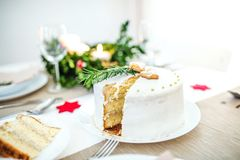 White a cake on table set for dinner at Christmas time. A white a cake on table set for dinner at Christmas time royalty free stock images