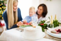 A white a cake on table set for dinner at Christmas time. A white a cake on table set for dinner at Christmas time, a family in the background royalty free stock photo