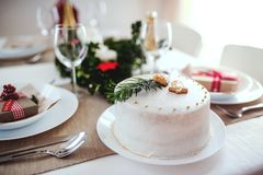 A cake on a table set for dinner at home at Christmas time. A white cake on a table set for dinner at home at Christmas time stock photos