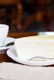 White cake on white dish with fork, napkin on table. Some image of white cake on white dish with fork, napkin on wood table at coffee shop, side view Stock Images