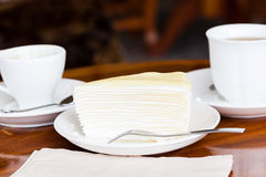 White cake on white dish with fork, napkin on table Stock Photography