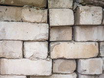 White calcium silicate bricks piled on top of each other. Old, cracked and chipped brick built, rough stack. The texture Royalty Free Stock Images
