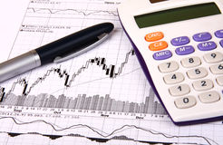 White calculator, a blue pen and a financial chart. White calculator and a blue pen lying on a financial chart Stock Photography