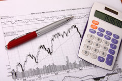 White calculator and a pen on a financial chart. White calculator and a red pen lying on a financial chart Royalty Free Stock Photos
