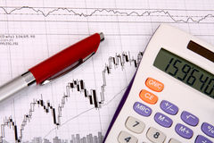 White calculator and a pen on a financial chart. White calculator and a red pen lying on a financial chart Royalty Free Stock Photography