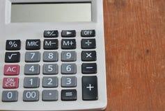 White calculator on wooden desk Stock Image