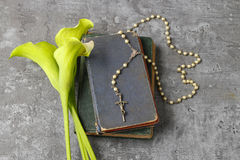 White calla flowers Zantedeschia, rosary and Holy Bible on sto. Ne background Stock Image
