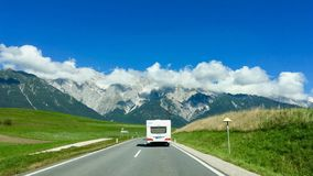 A white camper 7 caravan on a lonely road into the Swiss alps royalty free stock images