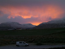 White camper van on the country road along the snow capped mountain range under beautiful sunset sky Stock Photography