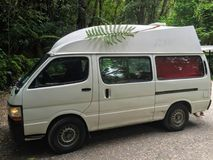 A white camper van in the forests of New Zealand, stamped with t stock photos