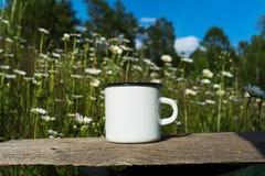 White campfire enamel mug mockup with daisy field stock photography