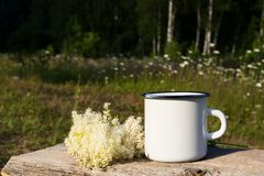 White campfire enamel mug mockup with white flowers. Campfire enamel coffee mug mockup with white wild flowers on the old timber. Empty mug mock up for design royalty free stock photo