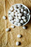White candies like sea pebbles on craft paper Stock Images