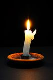 White candle against black background. Stock Image