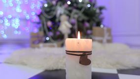 White candle on the background of Christmas tree. stock footage