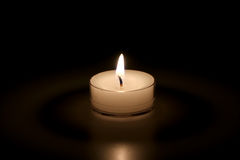 White Candle on a Black Background. A white tea light candle on a black background Royalty Free Stock Photography
